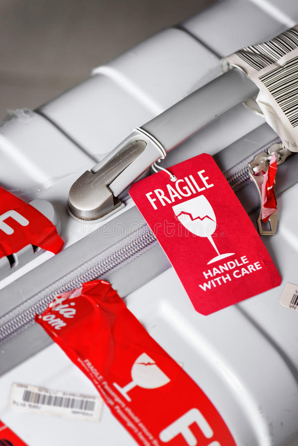 Closeup view of red luggage tag Fragile attached to suitcase. Nha Trang, Vietnam - August 16, 2016: Closeup view of bright red luggage tag Fragile, Handle with royalty free stock images