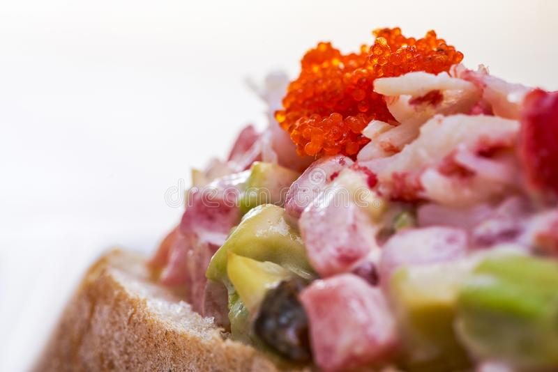 Closeup view of shrimp sandwich with tomato and red caviar on white blurred background. Homemade meal. stock photo