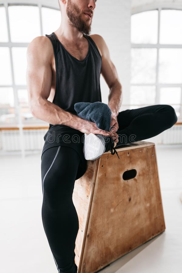 Closeup view on sweaty muscular man sitting on box in crossfit gym royalty free stock photos