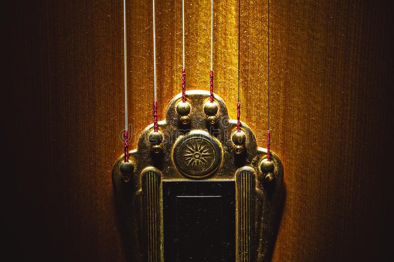 Tailpiece of Acoustic Guitar. Closeup view of tailpiece of an old dusty gypsy guitar stock photo