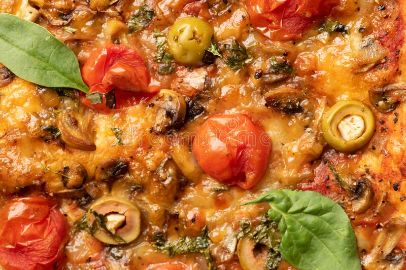 Top view of tasty pizza surface with tomato, olives garlic and spinach leaves stock images