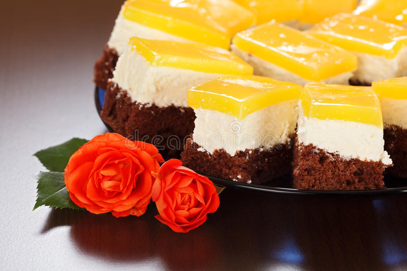 Closeup view of three-layered yoghurt cakes. With red roses on brown background stock image