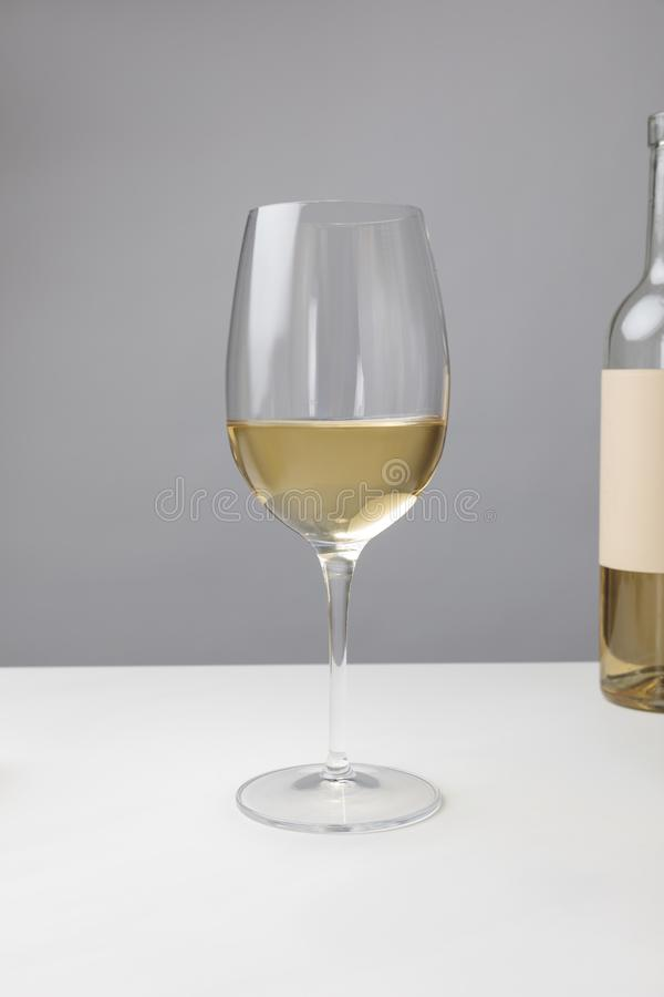 Closeup view of white wine glass and bottle on gray stock photography