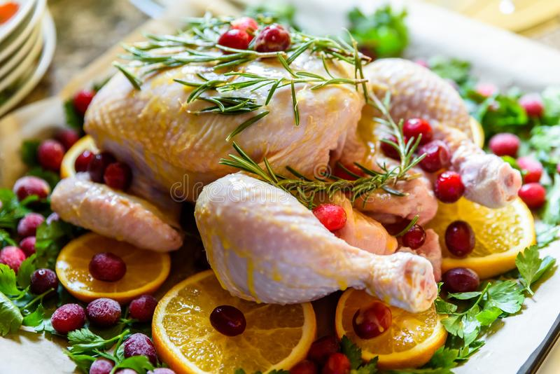 Closeup view of Whole Raw Chicken with Fresh parsley Cranberries and Orange Slices on baking tray tin prepared for roasting in ove. N stock images