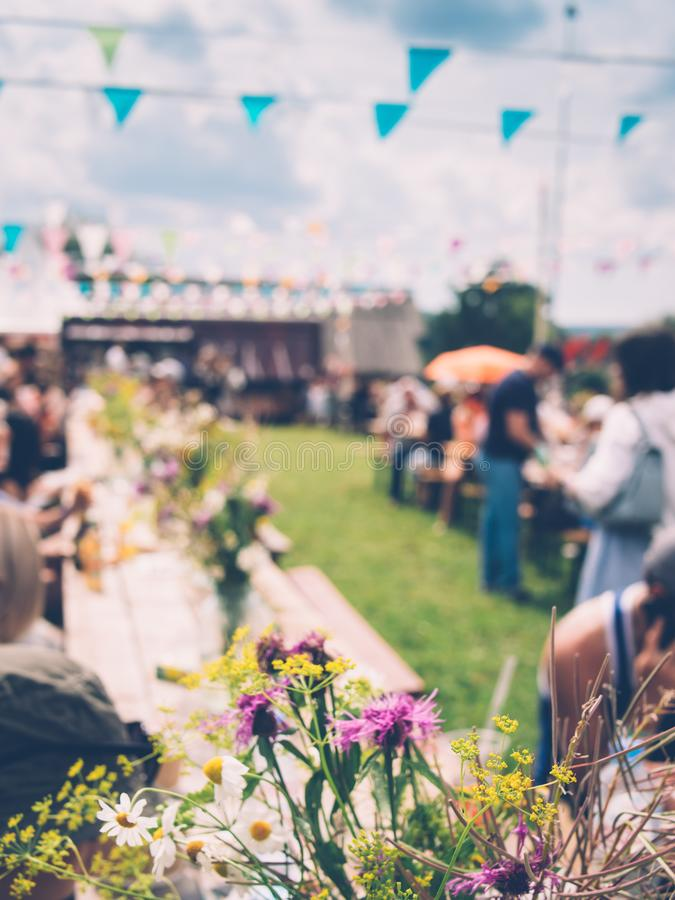 Closeup view of wild flowers on the table at summer country festival. Bouquets of wildflowers on wooden tables, green lawn, colourful flags against bright sky stock photo