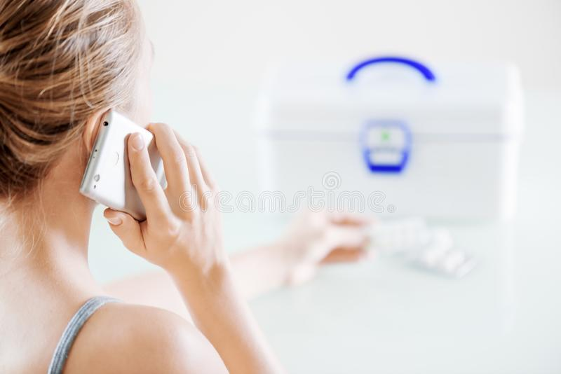 Closeup view of woman calling to doctor. First aid kit stock photo
