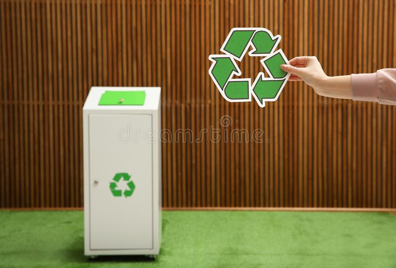 Closeup view of woman with recycling symbol and blurred trash bin on background. Space for text stock illustration