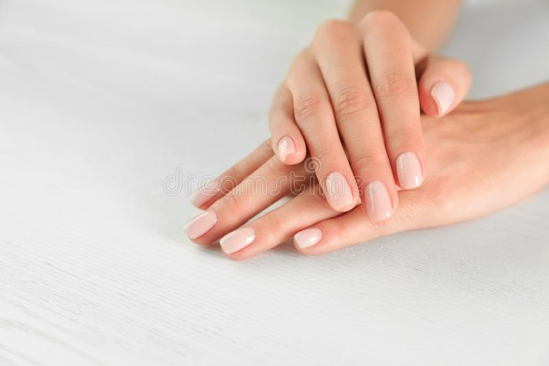 Closeup view of woman with smooth hands and manicure at table. Spa treatment royalty free stock image