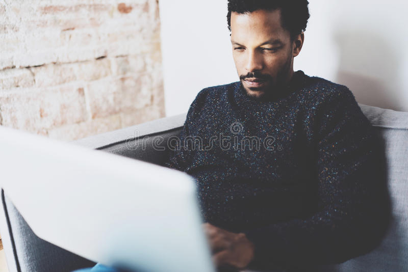 Closeup view of young African man using laptop while sitting sofa at his modern coworking studio.Concept full. Closeup view of young African man using laptop royalty free stock photo