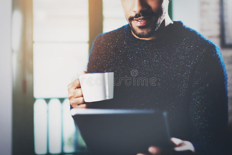 Closeup view of young bearded African man using tablet while holding white ceramic cup in hand at modern modern home royalty free stock images
