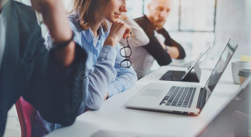 Closeup view of young Coworkers working together on new business deal at sunny meeting room.Horizontal.Blurred royalty free stock photography