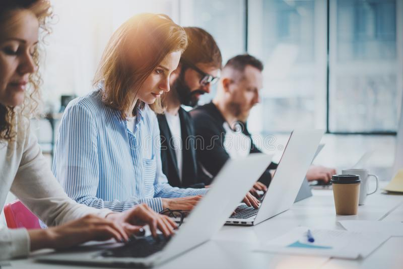 Closeup view of young Coworkers working together on new business presentation at sunny meeting room.Horizontal.Blurred stock image