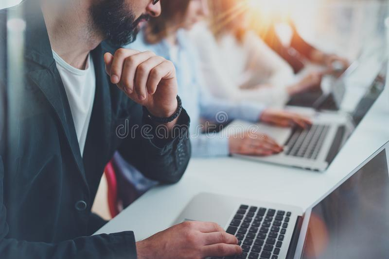 Closeup view of young Coworkers working together on new business presentation at sunny meeting room.Horizontal.Blurred royalty free stock photo