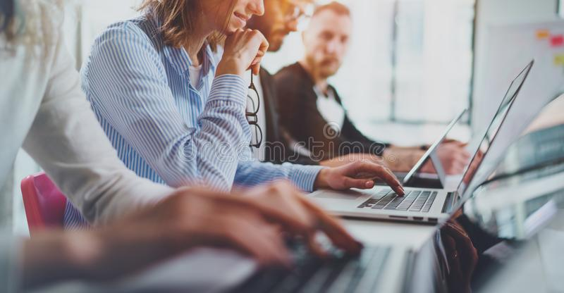 Closeup view of young Coworkers working together on new business presentation at sunny meeting room.Horizontal wide. stock images