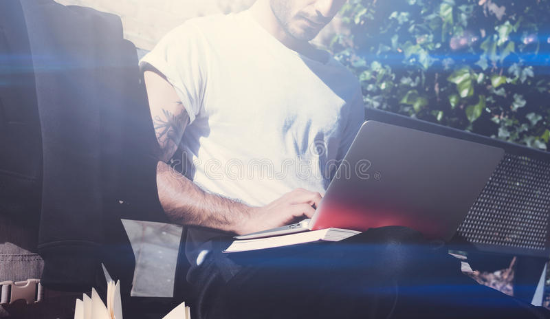 Closeup view of young man wearing white tshirt sitting on bench and working on notebook. Studying at the University stock photos