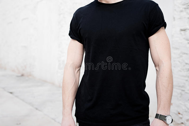Closeup view of young muscular man wearing black tshirt and jeans posing outside. Empty white wall on the background stock photography