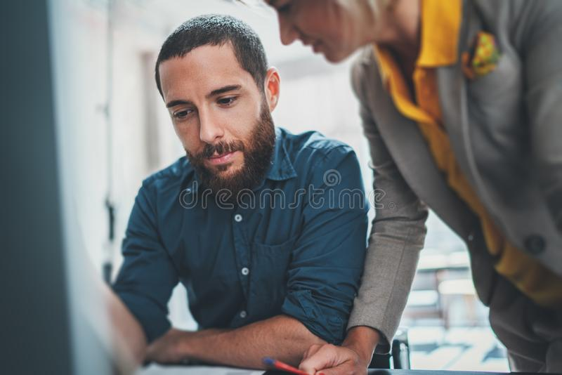 Closeup view of young professionals working together on new business presentation at sunny meeting room royalty free stock images