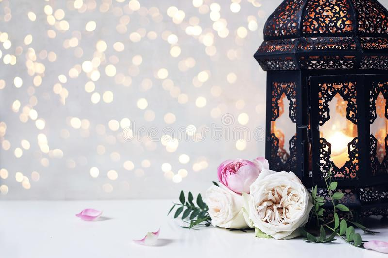 Closeup of vintage black Moroccan, Arabic lantern, glowing candle, green branches, rose flowers and petals on white. Table background, greeting card for Muslim stock images