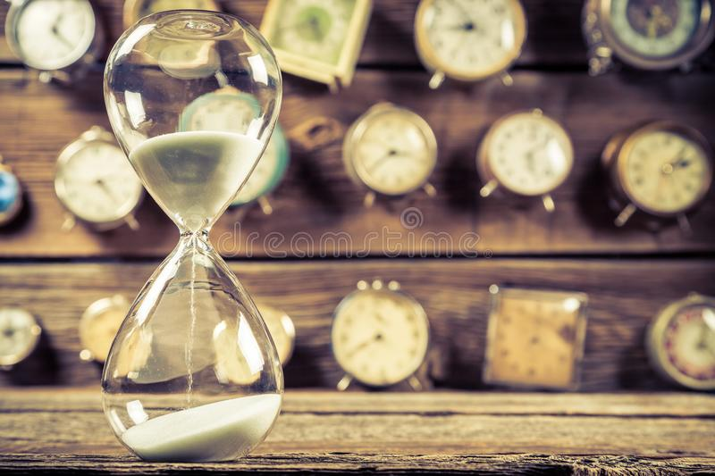 Vintage hourglass on background made of clocks royalty free stock images