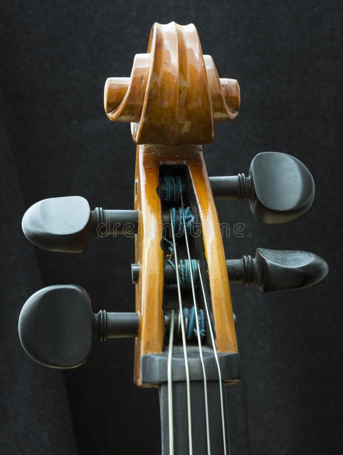 Closeup of part string instrument cello with snares and scroll. Closeup of vintage string instrument cello with snares and scroll royalty free stock photo