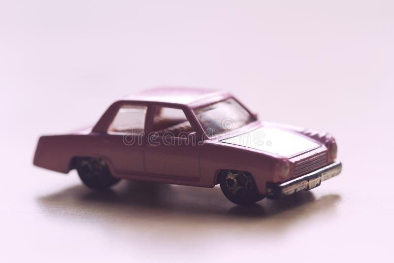 Closeup of vintage toy pink car. Horizontal sideview closeup of vintage toy pink car on light background selective focus stock image