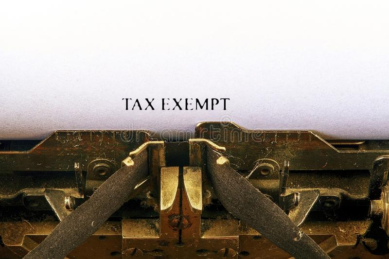 Closeup on vintage typewriter. Front focus on letters making TAX EXEMPT text. Business concept image with retro office tool.  royalty free stock photos