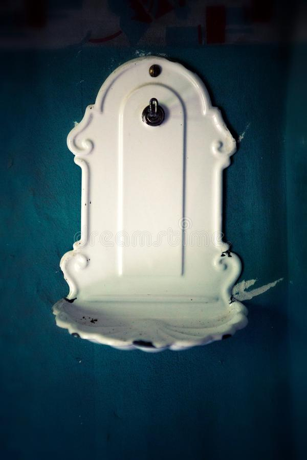 Closeup of vintage white porcelain soap dish. Mounted at wall royalty free stock images
