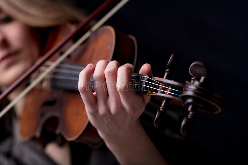 Closeup of a violinist`s hand playing. Young beautiful woman violinist player playing her instrument on her shoulder holding bow. portrait in a blurred dark room stock photos