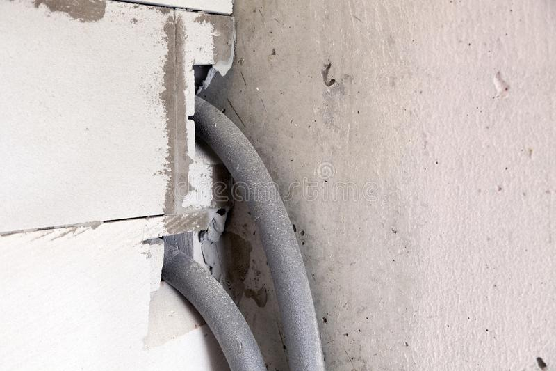 Closeup wall of gray aerated concrete with rough seams with hole for water pipes in isolation. Concept overhaul of apartment,. Closeup wall of gray aerated royalty free stock images