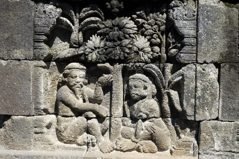 Stone carving. at Borobudur temple, Magelang, Indonesia. Closeup wall ornamented with bas-reliefs religion scene. Highly detailed stone carving. Borobudur stock image
