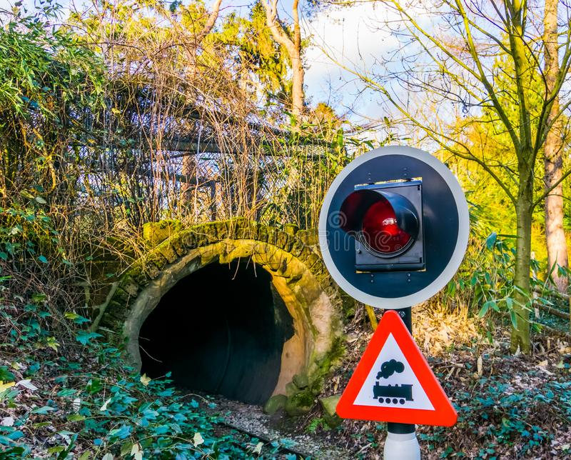 Closeup of a warning traffic light, railroad tunnel with warning sign stock photo