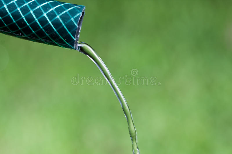 Closeup of water trickling from garden hose stock photo