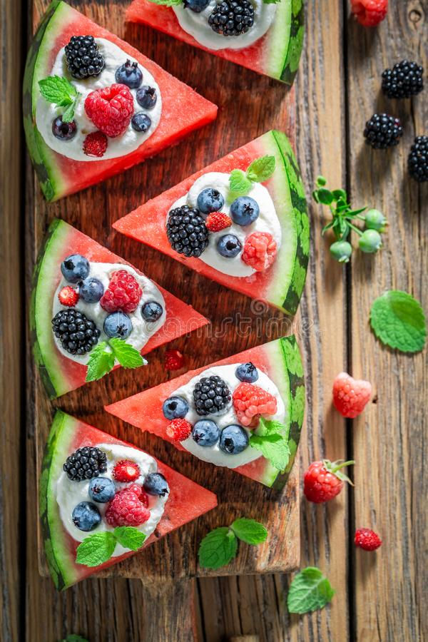 Closeup of watermelon pizza with whipped cream and fresh berries stock photos