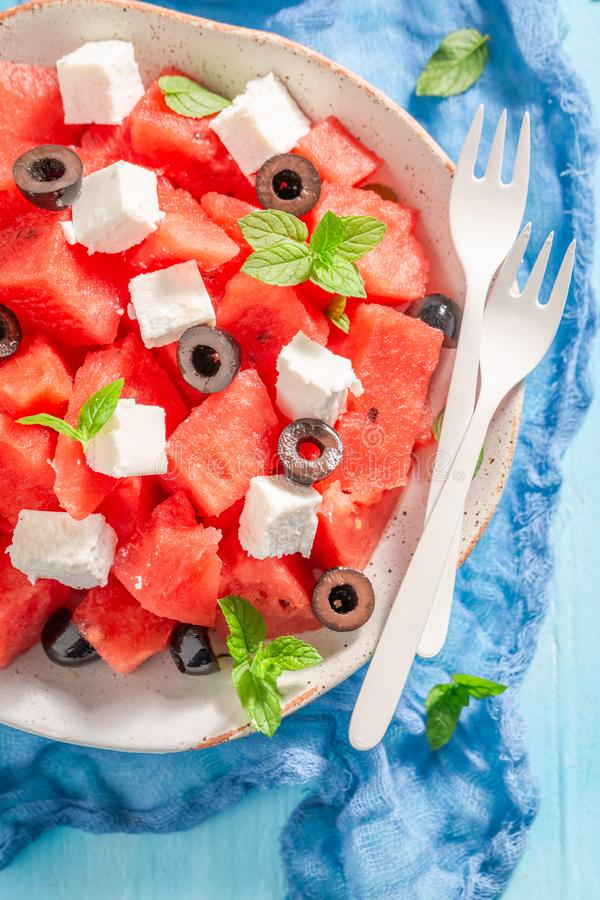 Closeup of watermelon salad with black olives and feta cheese. On blue table stock photos