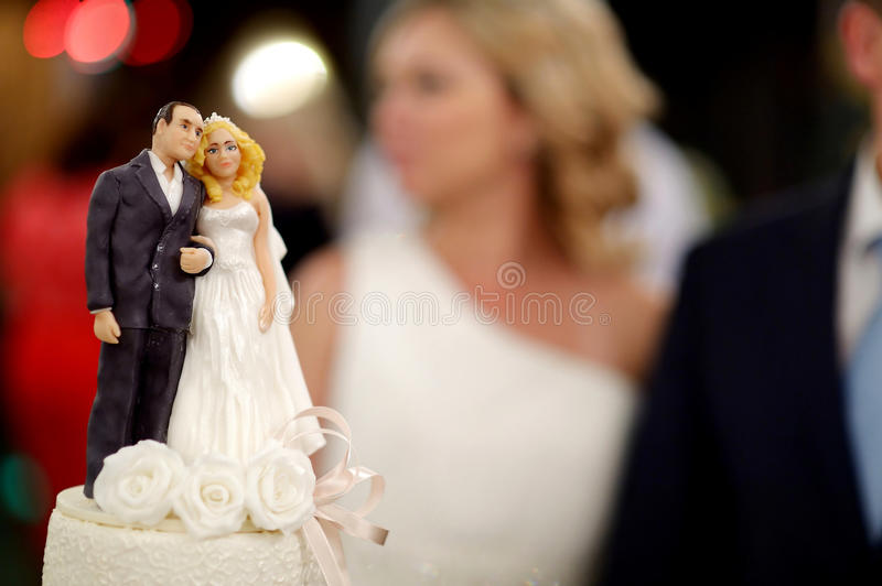 Closeup of wedding cake figurines at reception stock images