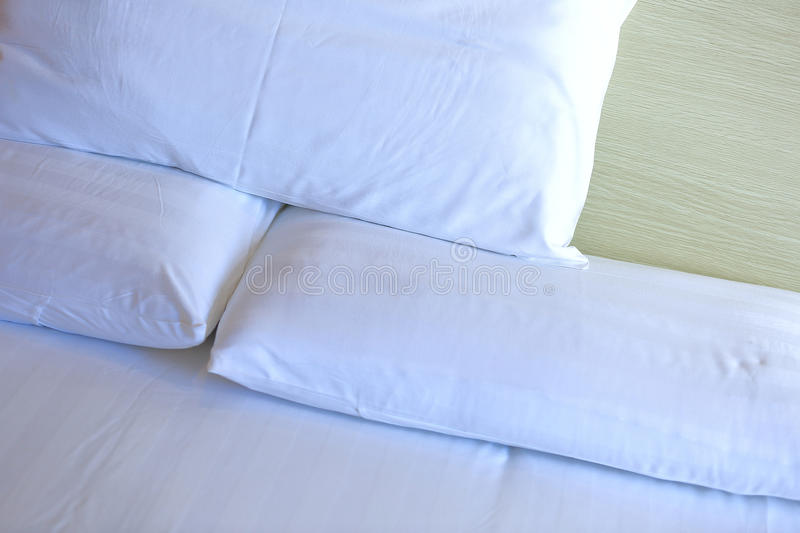 Closeup of white bedclothes and pillow. On bed stock image
