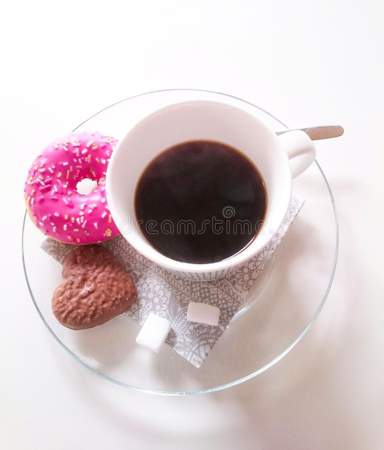 Closeup of a white ceramic coffee cup on a plate with a pink doughnut and heart-shaped cookie. A vertical overhead closeup of a white ceramic coffee cup on a royalty free stock image