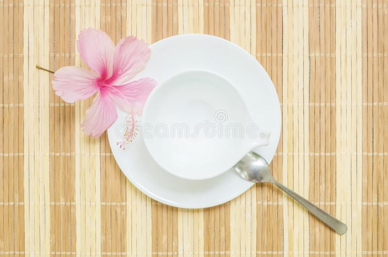 Closeup white ceramic cup for beverage with stainless spoon on blurred wood mat textured background. Closeup white ceramic cup for beverage with stainless spoon stock photos