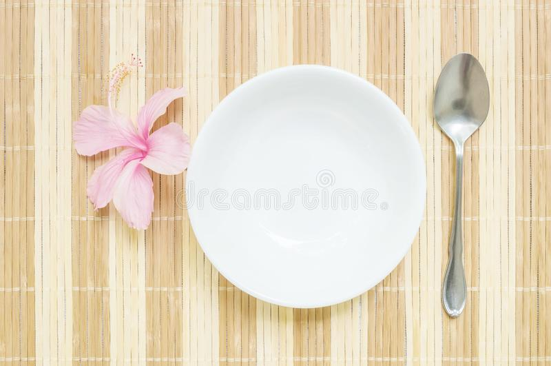 Closeup white ceramic cup for soup with stainless spoon and pink flower on blurred wood mat textured background. Closeup white ceramic cup for soup with royalty free stock image