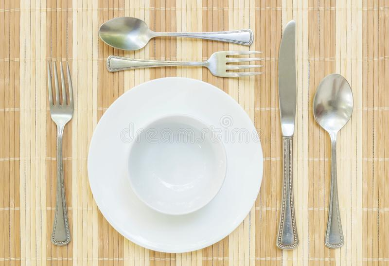 Closeup white ceramic dish and cup with stainless fork and spoon on wood mat textured background on dining table in top view ,. Closeup white ceramic dish and royalty free stock image