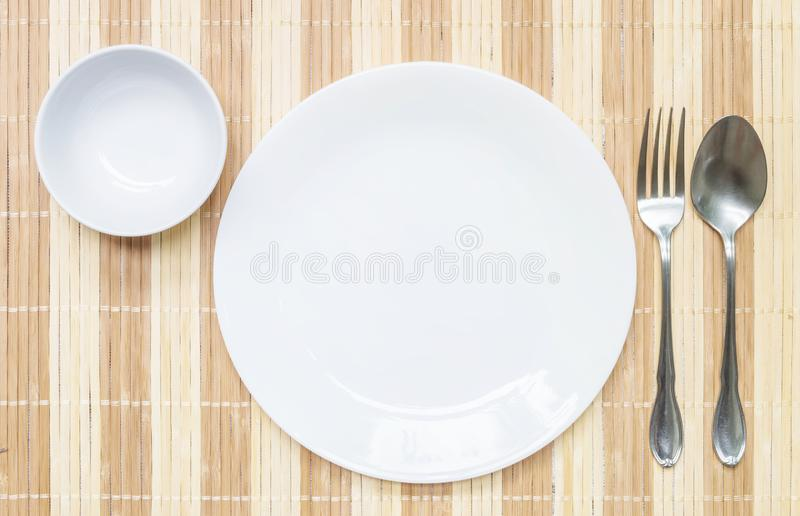 Closeup white ceramic dish and cup with stainless fork and spoon on wood mat textured background on dining table in top view ,. Closeup white ceramic dish and royalty free stock images