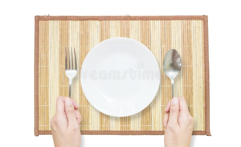Closeup white ceramic dish with stainless fork and spoon in woman hand on brown wood mat isolated on white background in top view. Closeup white ceramic dish royalty free stock photos