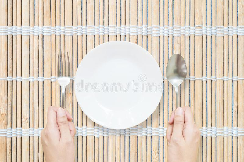 Closeup white ceramic dish with stainless fork and spoon in woman hand on wood mat textured background on dining table in top view. Closeup white ceramic dish stock photo