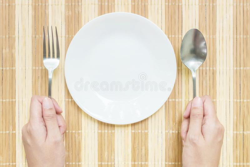 Closeup white ceramic dish with stainless fork and spoon in woman hand on wood mat textured background on dining table in top view. Closeup white ceramic dish stock image