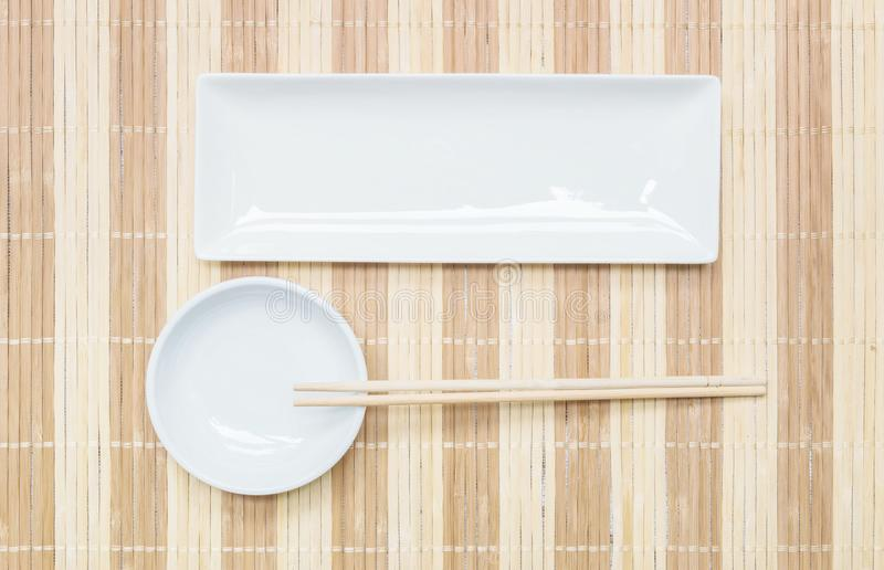 Closeup white ceramic square dish and chalice with wood chopsticks on wood mat textured background on dining table in top view royalty free stock photos