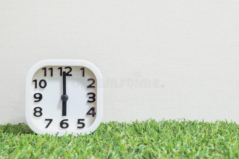 Closeup white clock for decorate in 6 o`clock on green artificial grass floor and cream wallpaper textured background with copy s stock photo
