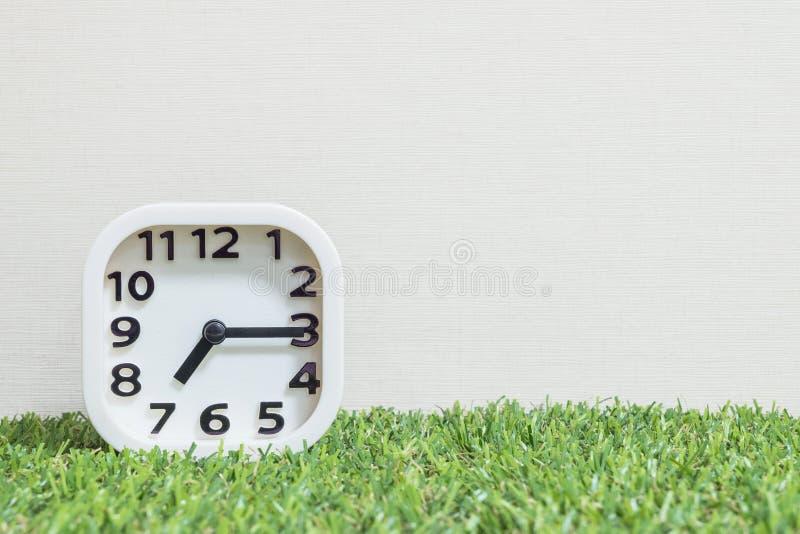 Closeup white clock for decorate show a quarter past seven or 7:15 a.m. on green artificial grass floor and cream wallpaper textur. Closeup white clock for stock photos