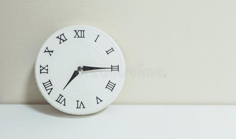 Closeup white clock for decorate show a quarter past seven or 7:15 a. m. on white wood desk and cream wallpaper textured backgroun. D with copy space royalty free stock images