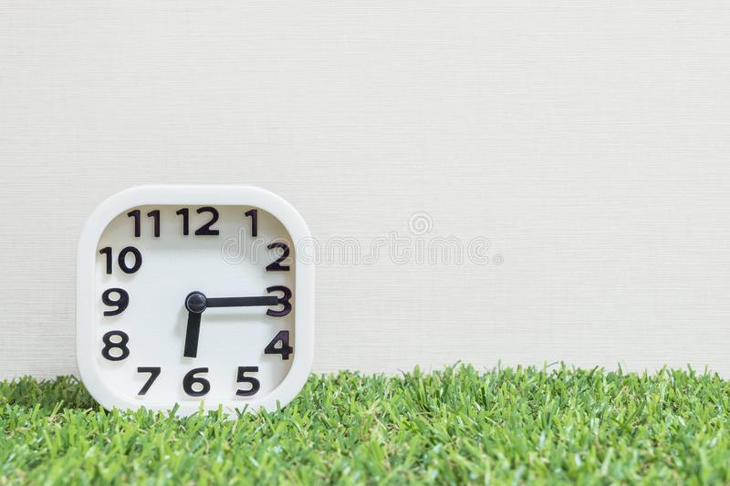 Closeup white clock for decorate show a quarter past six or 6:15 a.m. on green artificial grass floor and cream wallpaper textured. Background stock photography