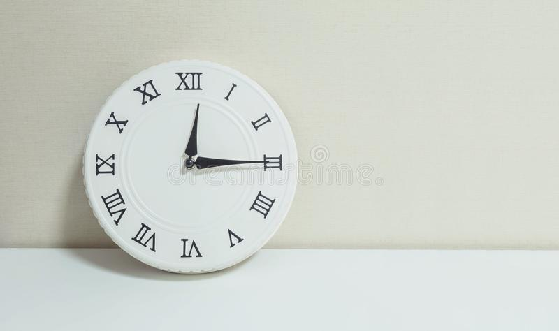 Closeup white clock for decorate show a quarter past twelve or 12:15 a.m. on white wood desk and cream wallpaper textured backgrou royalty free stock photography